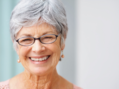 Closeup of a pretty smiling gray haired woman with copyspace
